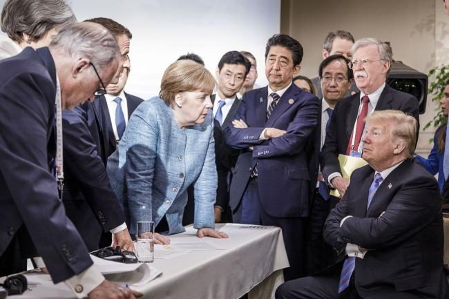 © Bloomberg. Angela Merkel deliberates with Donald Trump at the G-7 summit in Charlevoix, Canada in 2018. Photographer: Handout/Getty Images