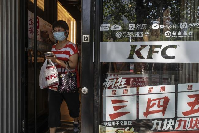 © Bloomberg. A customer exits a KFC restaurant operated by Yum China Holdings Inc. in Beijing, China. Photographer: Gilles Sabrie/Bloomberg