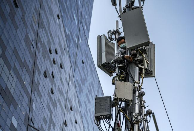 © Bloomberg. BEIJING, CHINA - APRIL 23: A Chinese technician wears a protective mask as he installs a new Huawei 5G station on a tower in a business district on April 23, 2020 in Beijing, China. After decades of growth, officials said Chinas economy had shrunk in the latest quarter due to the impact of the coronavirus epidemic. The slump in the worlds second largest economy is regarded as a sign of difficult times ahead for the global economy. While industrial sectors in China are showing signs of reviving production, a majority of private companies are operating at only 50% capacity, according to analysts. With the pandemic hitting hard across the world, officially the number of coronavirus cases in China is dwindling, ever since the government imposed sweeping measures to keep the disease from spreading. Officials believe the worst appears to be over in China, though there are concerns of another wave of infections as the government attempts to reboot the worlds second largest economy. Since January, China has recorded more than 81,000 cases of COVID-19 and at least 3200 deaths, mostly in and around the city of Wuhan, in central Hubei province, where the outbreak first started. (Photo by Kevin Frayer/Getty Images)