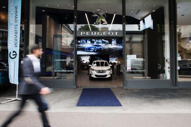 © Bloomberg. A pedestrian passes the PSA Retail Saint Didier automobile showroom in Paris.