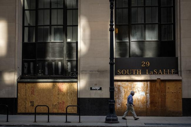 © Bloomberg. A pedestrian wearing a protective mask passes up a boarded-up store in Chicago. Photographer: Christopher Dilts/Bloomberg