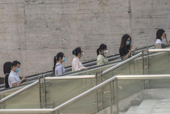 © Bloomberg. Morning commuters wearing protective masks ride on an escalator at a plaza in downtown Guangzhou, China, on Wednesday, May 13, 2020. The Pearl River Delta industrial belt has served as one of China's most important growth engines since the Communist Party opened the economy four decades ago, propelling its rise to become one of the world's leading powers. But now in Guangdong the situation is getting dire in some labor-intensive sectors where the widespread struggle to earn cash risks turning into a big political problem for Chinese President Xi Jinping. Photographer: Qilai Shen/Bloomberg