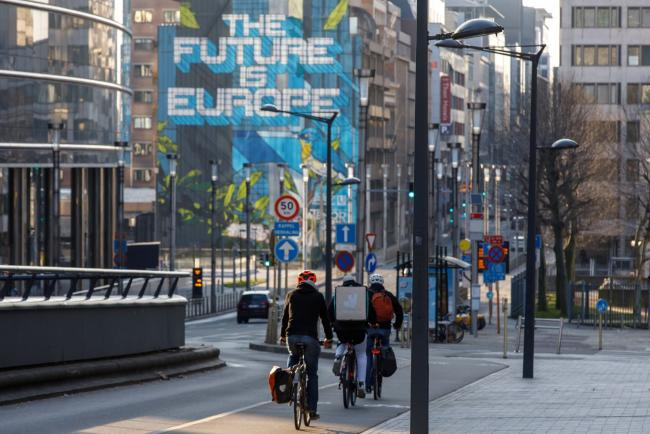 © Bloomberg. Bicyclists ride near the Berlaymont building in Brussels, Belgium. Photographer: Olivier Matthys/Bloomberg