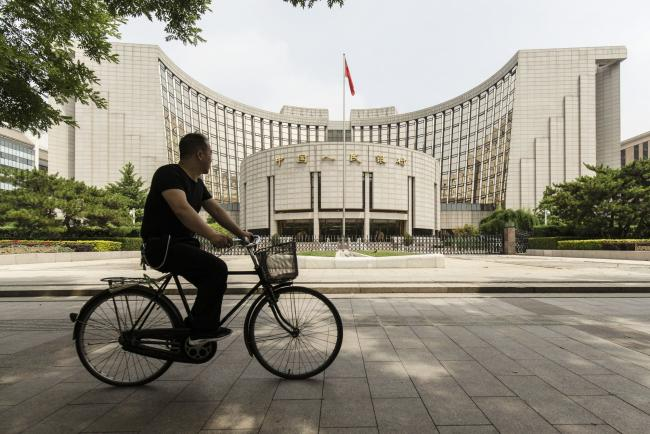 © Bloomberg. A man rides a bicycle past the People's Bank of China (PBOC) headquarters in Beijing, China, on Friday, June 7, 2019. China's central bank governor said there's
