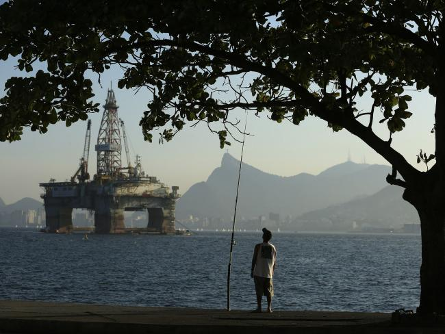 © Bloomberg. A man fishes in Guanabara Bay while an oil drilling platform floats in the background near Niteroi, Brazil. Photographer: Dado Galdieri/Bloomberg