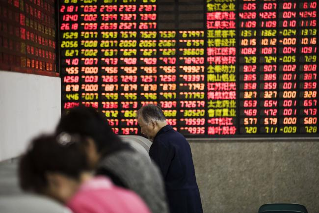 © Bloomberg. Investors stand at trading terminals in front of electronic stock boards at a securities brokerage in Shanghai, China, on Friday, Oct. 13, 2017. A number of economic indicators show
