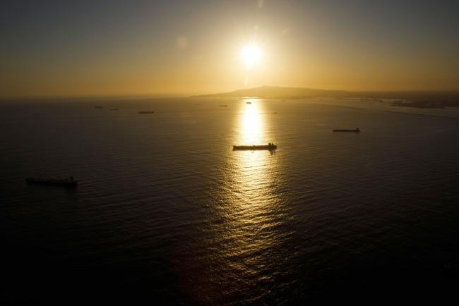 © Bloomberg. Oil tankers are seen anchored in the Pacific Ocean as the sun sets in this aerial photograph taken above Long Beach, California, U.S., on Friday, May 1, 2020. The volume of oil on vessels located just offshore the state peaked at 26 million barrels over the weekend, about a quarter of the world's daily consumption, before dropping to 22 million barrels on Monday, according to Paris-based Kpler SAS, which tracks tanker traffic. Photographer: Patrick T. Fallon/Bloomberg
