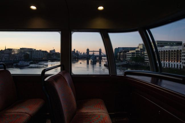 © Bloomberg. Tower Bridge stands in this view frame by a window on an empty bus traveling through the City of London, U.K., on Friday, May 29, 2020. For the last 11 weeks, Europe's financial center has been staffed with skeleton crews, particularly on the high-speed trading desks that are difficult to run from home. Photographer: Hollie Adams/Bloomberg