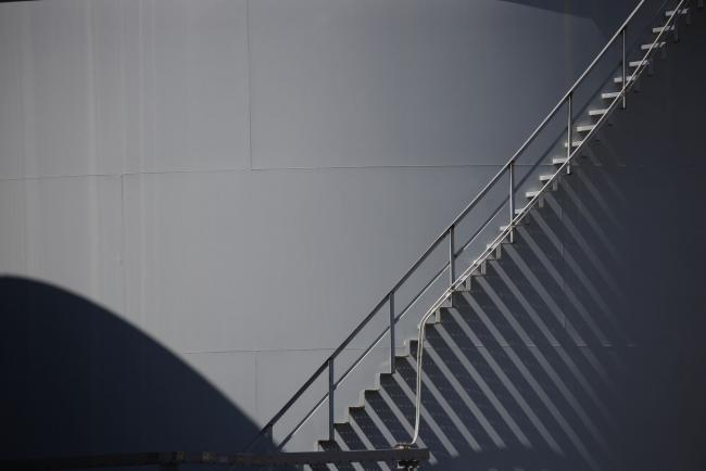 © Bloomberg. A staircase ascends a storage tank located near a dock for Hornbeck Offshore Services, Inc. oil industry support vessels in Port Fourchon, Louisiana, U.S., on Thursday, June 11, 2020. Oil eclipsed $40 a barrel in New York on Friday, extending a slow but relentless rise that's been fueled by a pick-up in demand and could signal a reawakening for U.S. shale production. Photographer: Luke Sharrett/Bloomberg