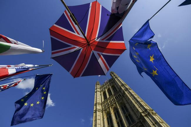 © Bloomberg. An umbrella featuring the design of the Union flag, also known as the Union Jack, stands near European Union (EU) flags outside the Houses of Parliment in London, U.K., on Tuesday, Oct. 22, 2019. U.K. Prime Minister Boris Johnson will find out Tuesday evening whether he has any chance of getting his Brexit deal through Parliament -- and whether he can do it ahead of his Oct. 31 deadline. Photographer: Chris J. Ratcliffe/Bloomberg
