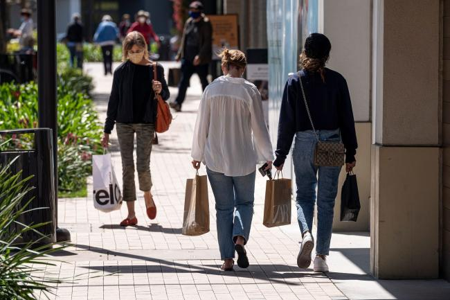 © Bloomberg. Shoppers wearing protective masks carry bags in the Broadway Plaza Shopping Center in Walnut Creek, California, U.S., on Wednesday, April 14, 2021. U.S. retail sales probably swelled in March thanks to faster hiring, the distribution of federal stimulus checks, a steady pace of Covid-19 vaccinations and fewer restrictions on stores across the country. Photographer: David Paul Morris/Bloomberg