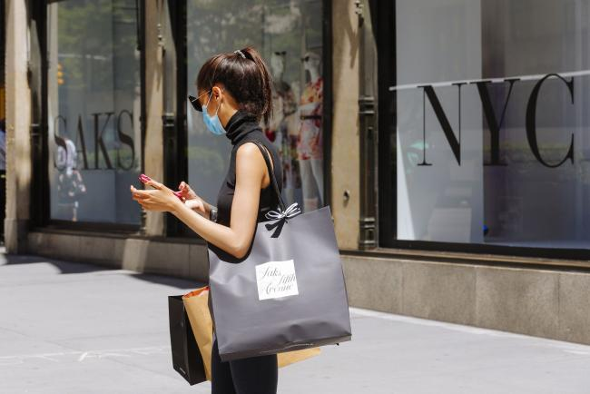 © Bloomberg. A pedestrian wearing a protective mask carries a shopping bag outside the Saks Fifth Avenue store New York, U.S., on Wednesday, June 24, 2020. New York, New Jersey and Connecticut will require visitors from virus hot spots to quarantine for 14 days Photographer: Angus Mordant/Bloomberg