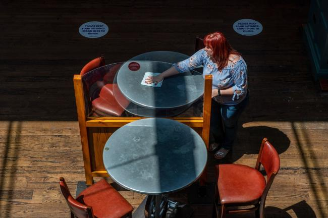 © Bloomberg. An employee cleans tables divided by a perspex screen at The Mossy Well pub, operated by J D Wetherspoons Plc, in this arranged photograph in London, U.K., on Wednesday, June 24, 2020. Hotels, pubs, restaurants and cinemas will be able to open their doors from July 4, U.K. Prime Minister said as he gave the green light for England's beleaguered tourism and hospitality industry to restart.