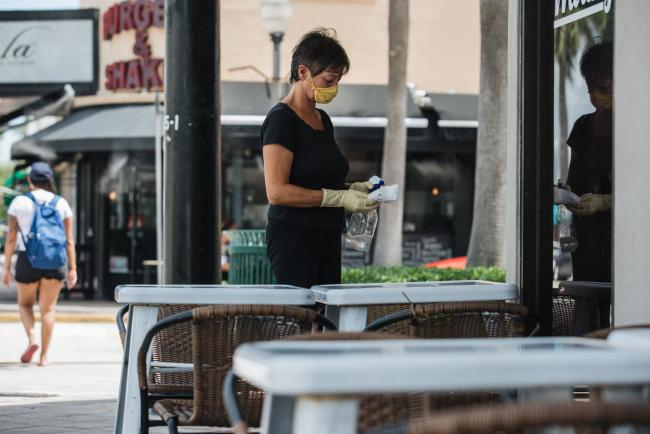 © Bloomberg. An employee wearing a protective mask and gloves at sanitizes a table in the outdoor dining area of a restaurant in Miami, Florida, U.S., on Wednesday, July 8, 2020. A day after announcing pending closures, Mayor Gimenez said he had met with medical experts and business leaders and decided that restaurants could still provide outdoor dining and gyms could open if everyone wore a mask.