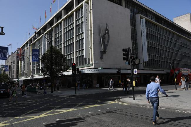 © Bloomberg. A pedestrian crosses Oxford Street outside the John Lewis Partnership Plc department store in London.