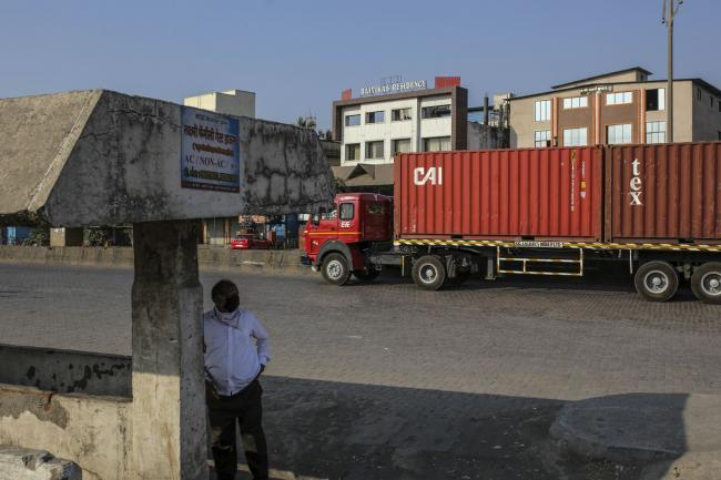© Bloomberg. A truck transports shipping containers from the Jawaharlal Nehru Port, operated by Jawaharlal Nehru Port Trust (JNPT), in Navi Mumbai, Maharashtra, India, on Monday, March 30, 2020. As billions of people stay home in the the world's major economic centers, consumption of everything from transport fuel to petrochemical feedstocks is in freefall. Refiners that have already been filling up their storage tanks with unsold products now have little choice but to partially shut down their plants. Photographer: Dhiraj Singh/Bloomberg