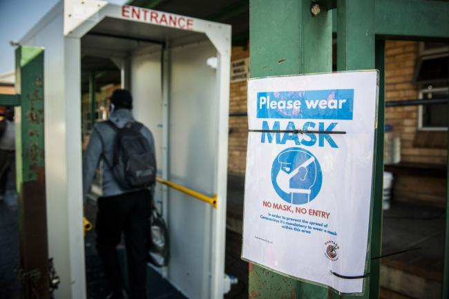© Bloomberg. A sign advising passengers must wear protective face masks hangs on a beam at the Randburg taxi rank in Johannesburg on May 14. Photographer: Waldo Swiegers/Bloomberg