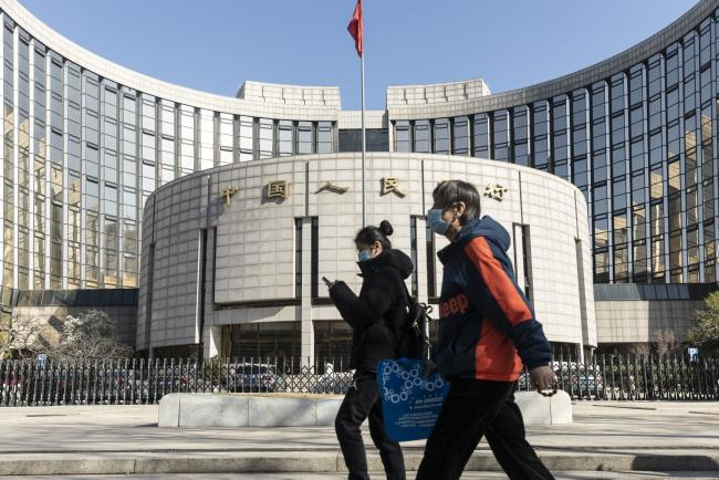 © Bloomberg. Pedestrians wearing protective masks walk past the People's Bank of China (PBOC) building in Beijing, China, on Tuesday, March 17, 2020. China suffered an even deeper slump than analysts feared at the start of the year as the coronavirus shuttered factories, shops and restaurants across the nation, underscoring the fallout now facing the global economy as the virus spreads around the world. Photographer: Qilai Shen/Bloomberg