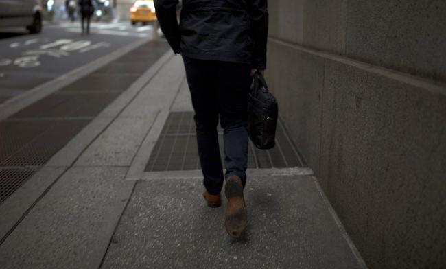 © Bloomberg. A pedestrian walks along a street near the New York Stock Exchange. Photographer: Jordan Sirek/Bloomberg